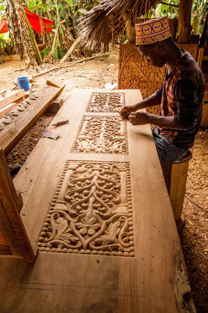 Zanzibar, Tanzania, March 29, 2018. one african man wood carve doing the the work makes a beautiful carver door. Traditional African art