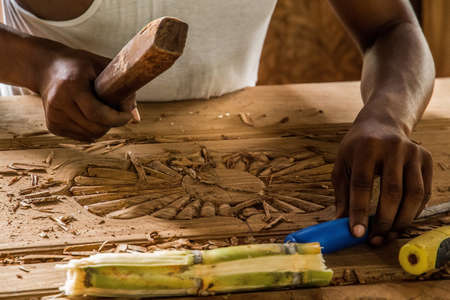 Zanzibar, Tanzania, March 29, 2018. one african man wood carve doing the the work makes a beautiful carver door. Traditional African art Фото со стока - 133911804