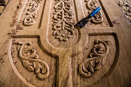 Zanzibar, Tanzania, March 29, 2018. one african man wood carve doing the the work makes a beautiful carver door. Traditional African art Фото со стока - 133911806