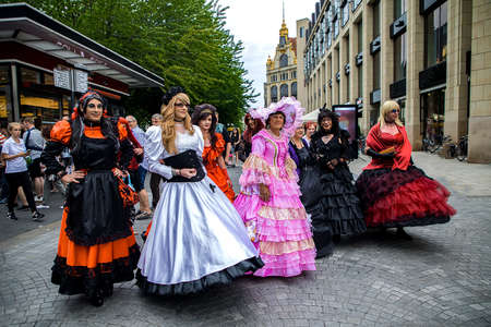 Leipzig, Germany , Juny 9, 2019 . Festive people in black and red gothic  and steampunk costumes at the street. Men dressed in women dresses