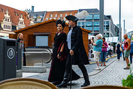 Leipzig, Germany , Juny 9, 2019 . Festive people in black and red gothic  and steampunk costumes at the street Фото со стока - 133911978