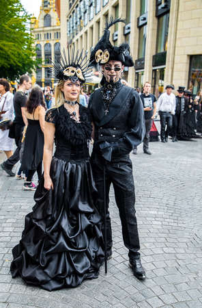Leipzig, Germany , Juny 9, 2019 . Festive people in black and red gothic  and steampunk costumes at the street Фото со стока - 133912003