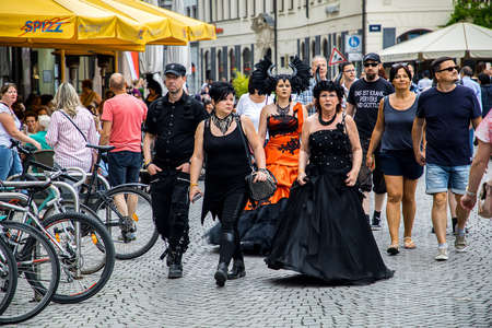 Leipzig, Germany , Juny 9, 2019 . Festive people in black and red gothic  and steampunk costumes at the street Фото со стока - 133912007