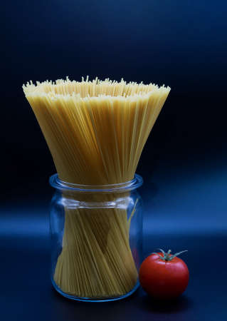 spaghetti standing in a trasparent glass jar on a blue background and a ripe tomato lying next to the can is close shot in the studio
