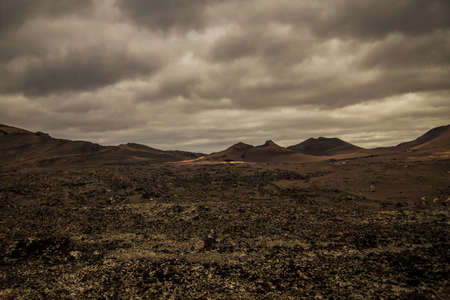 incredibly beautiful volcanoc landscape with black sand and red mountains and a beautiful sky during the day on the spanish island of Canary Lanzarote