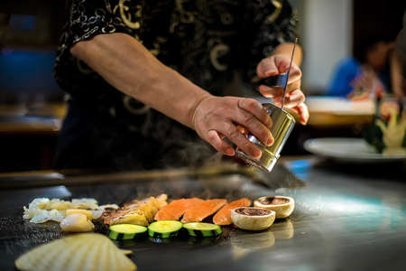 teppan show in a Japanese restaurant, cooking directly in front of the client, fish, rice, meat, vegetables