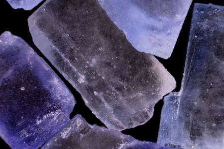super makro shot of several crystals of white-blue persian iranian salt isolated on black background