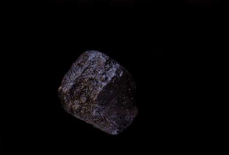 super macro shot single crystal black hawaiian salt very close on black background isolated Фото со стока
