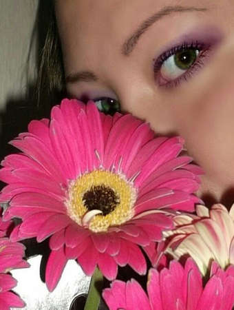 oriental girl: Oriental girl looks at the camera covering her face with a bouquet of flowers Stock Photo