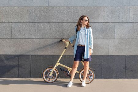 One beautiful woman stands near a stone wall and holds a folding bike, looks at the sun.