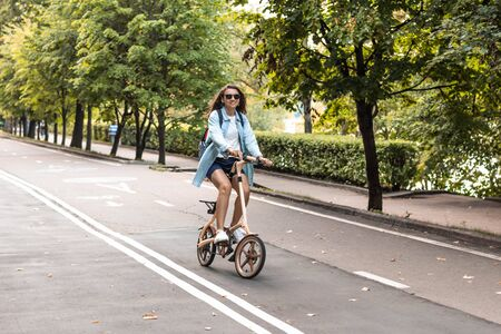 Happy white woman in sunglasses and in casual wear rides a folding bike in the park on a warm day on a background of foliage. Summer or spring lifestyle.