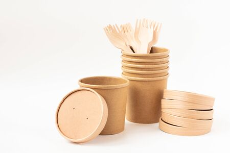 Eco friendly paper dishes. Still life with craft cups, caps, wooden forks. Recyclable tableware for fast food. Copy space. Archivio Fotografico