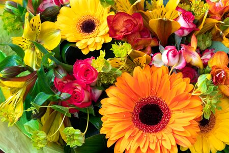 Bright yellow and orange gerbera in a bouquet of flowers. Beautiful bouquet gift for the holiday. Flowering plants as a postcard. Imagens