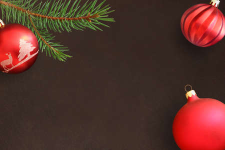 Dark background with Christmas fir branch, red and wavy dull ball. Top view. Stock Photo