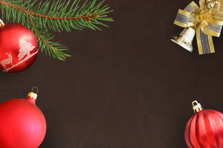 dull: Christmas fir branch, red wavy and dull ball and bell on a dark background Stock Photo