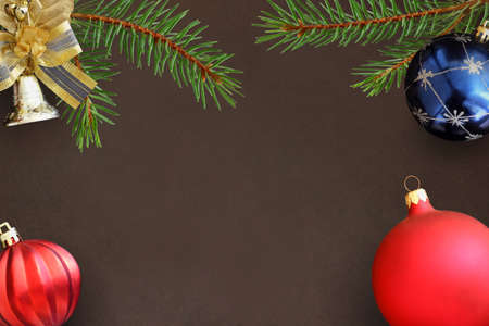 dull: Christmas branches of spruce, blue and red wavy dull balloon and decorative bell on dark background Stock Photo