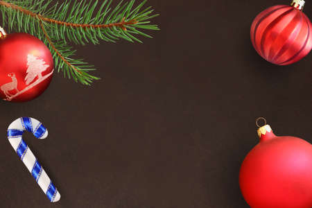 dull: Dark background with Christmas fir branch, stick, red and wavy dull ball. Top view. Stock Photo