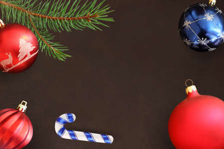 dull: Dark background with Christmas fir branch, stick, red wavy dull and blue ball Stock Photo