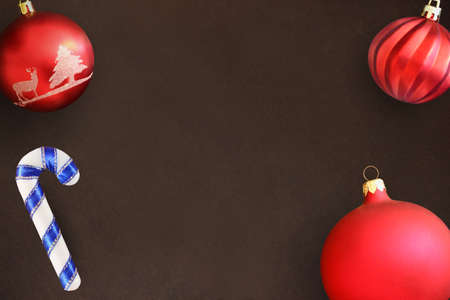dull: Christmas red and wavy dull balls, stick on dark wooden table. Top view. Stock Photo