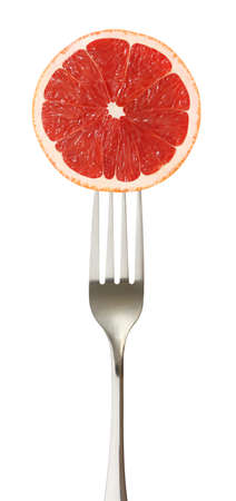 Grapefruit cut piece on impaled on a fork isolated on white background.