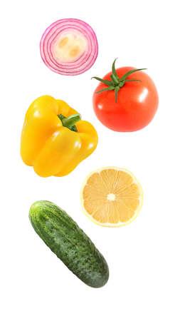 Falling flying vegetables bell pepper, onion, lemon, cucumber, tomato isolated on white background 写真素材