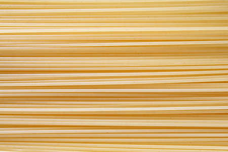 Spaghetti pasta vermicelli raw background lined in a row