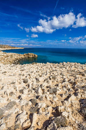 Sea coast with clear turquoise water and sharp stones on cape Cavo Greco, Cyprus.