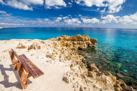 Rocky coast, bench on the shore and clear sea turquoise water at Cape Cavo-Greco, Cyprus. Banco de Imagens