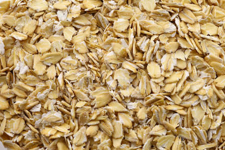 Oatmeal flakes raw in bulk, cereal plants. Full depth of field. Healthy breakfast and nutrition concept.