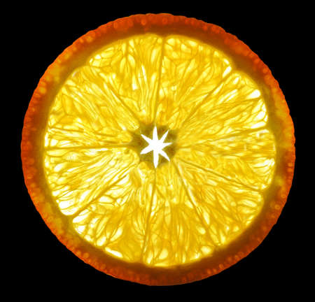 Orange fruit cut a thin transparent piece on a gleam in the background light isolated on black background