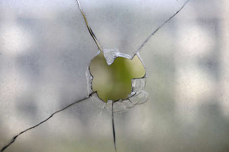 A round hole in the glass broken by a rock or bullet. 版權商用圖片