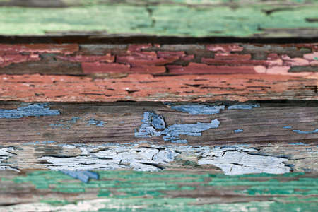 Old dried paint on wooden planks, red, green, blue,