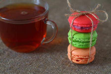 Macaroons multicolored and a glass cup of tea on a table with a burlap tablecloth