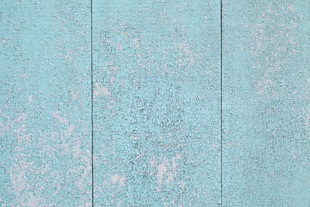 Background with peeling old blue paint, wooden planks vertical.