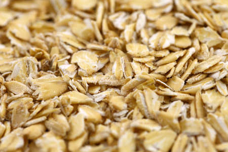 Oatmeal flakes raw in bulk, cereal plants, a healthy breakfast and nutrition concept.