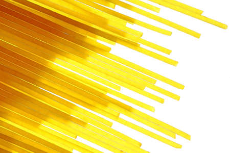 Spaghetti or pasta raw thin transparent piece on a gleam in the background light isolated on black background