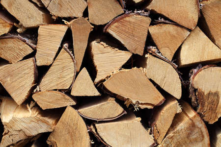 Hardwood firewood split logs stacked in a pile, an end view. 版權商用圖片
