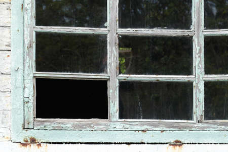 Old dirty wooden window frame without one glass.