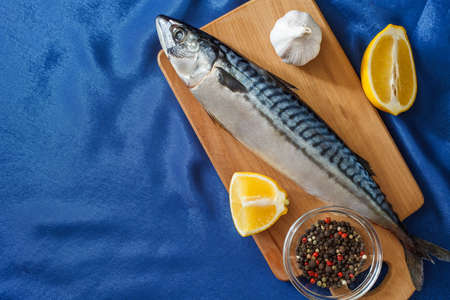 Raw mackerel fish raw, cutting board, lemons, peppers, spices, garlic and a blue satin tablecloth. Top view with copy space.