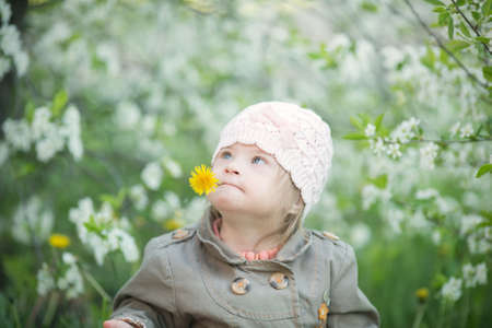 little girl with Down syndrome smelling flowers