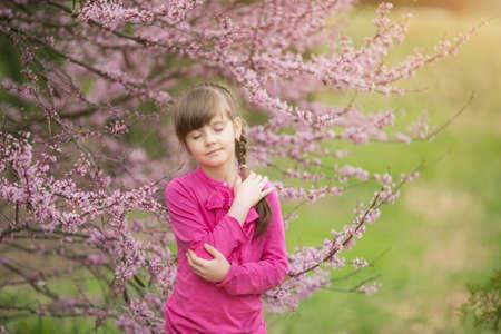beautiful gentle girl standing in a lush garden Stock Photo