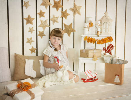 girl sitting near the Christmas gifts photo