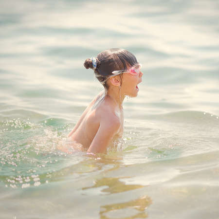 little girl swims and dives to the sea photo