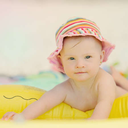cheerful little baby girl with Downs Syndrome playing in the pool