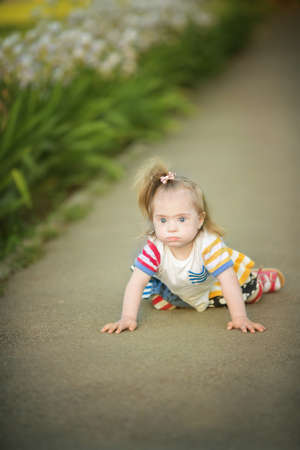 funny little girl with Down syndrome creeps along the path Stock Photo
