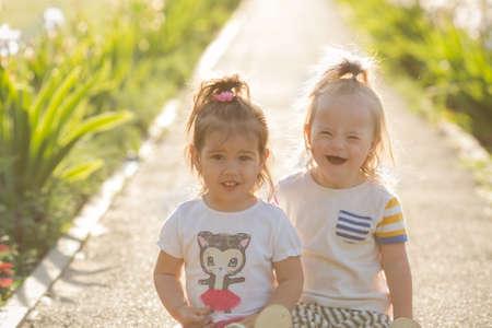portret van een lachend meisje met het syndroom van Down en vriendinnen