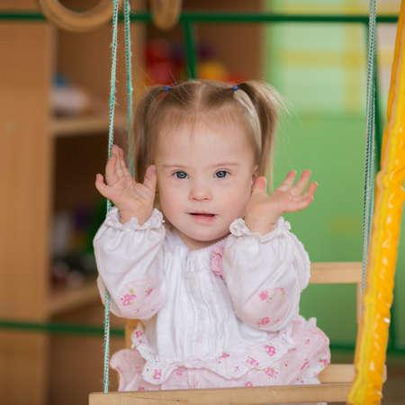 Niña con síndrome de Down jugando a las escondidas Foto de archivo - 30865879
