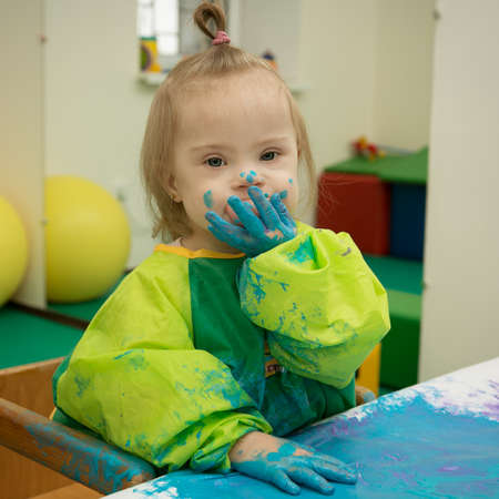 Girl with Down syndrome is busy painting photo