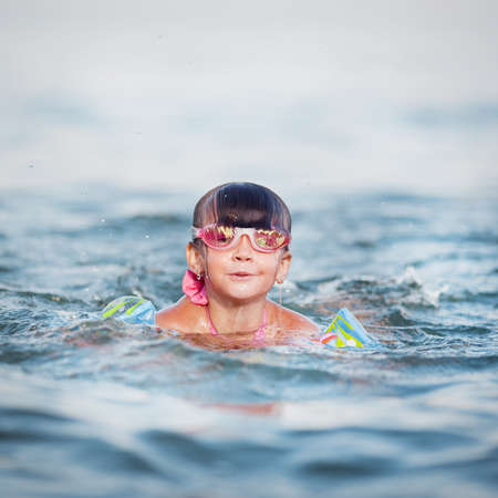 little girl swims and dives to the sea Stock Photo