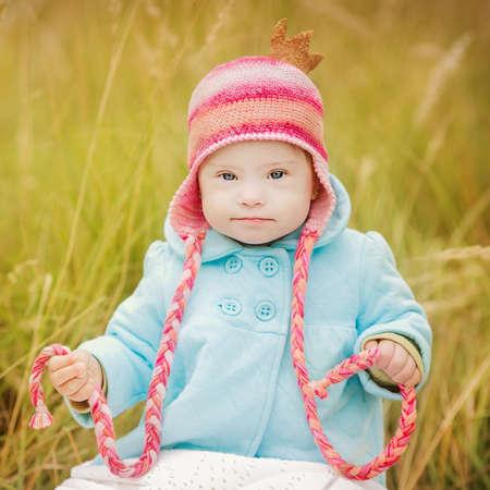 秋の公園で座っているダウン症候群を持つ美しい女の子 写真素材 - 30865888